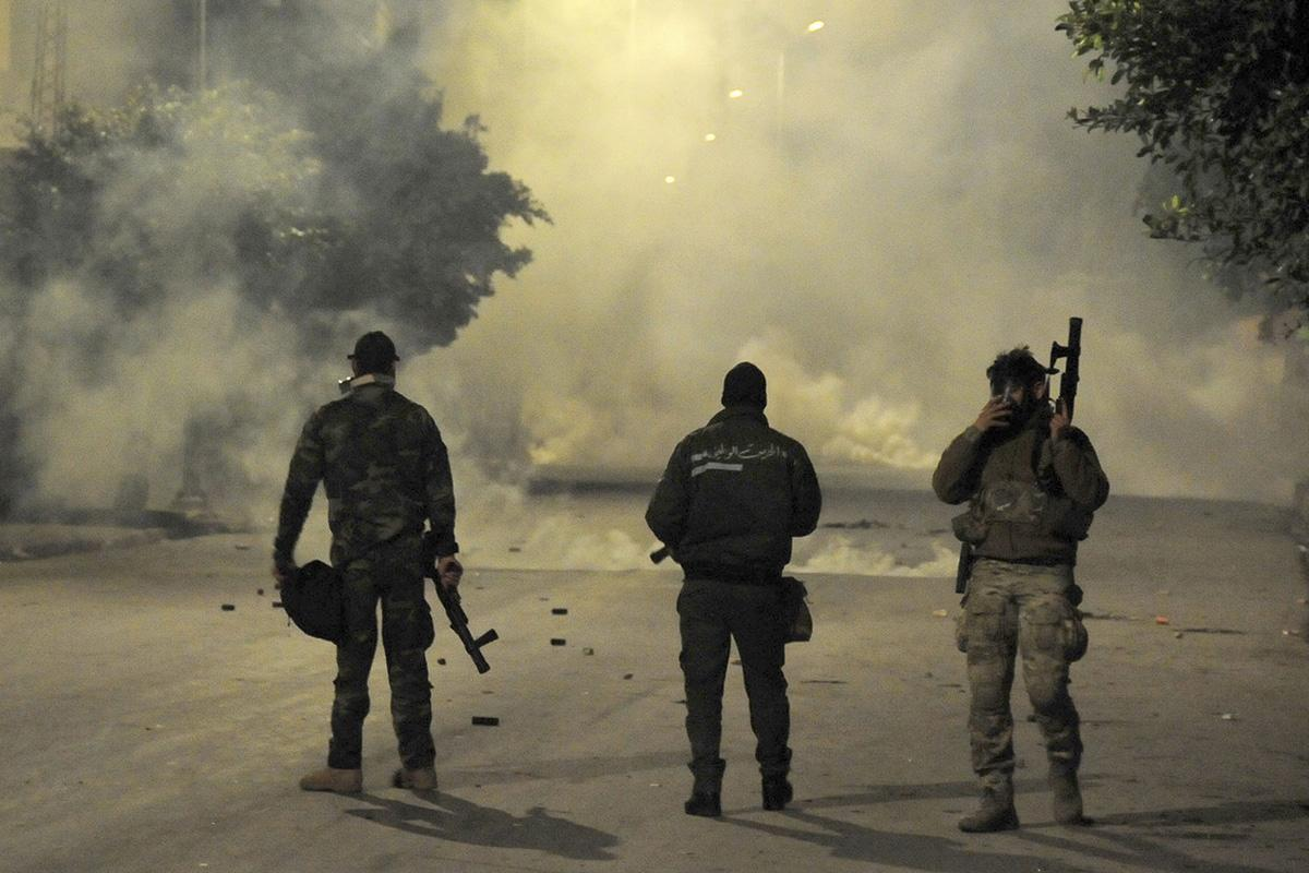 Police officers face demonstrators in Ettadhamen City near Tunis, Tunisia, on Tuesday.