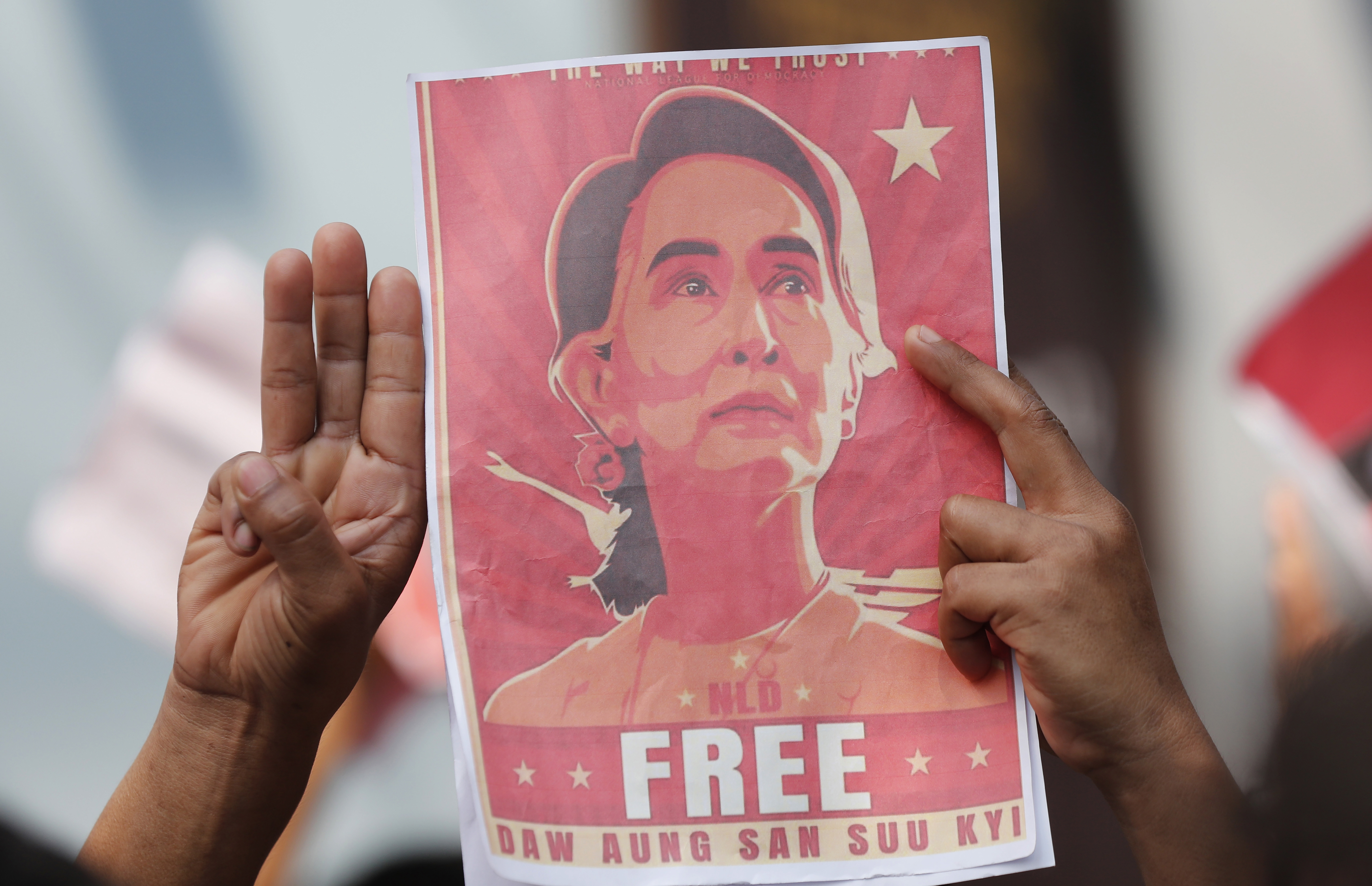 In this Feb. 8 photo, a Myanmar national in Bangkok, Thailand, holds a poster protesting the detention of Myanmar leader Aung San Suu Kyi.