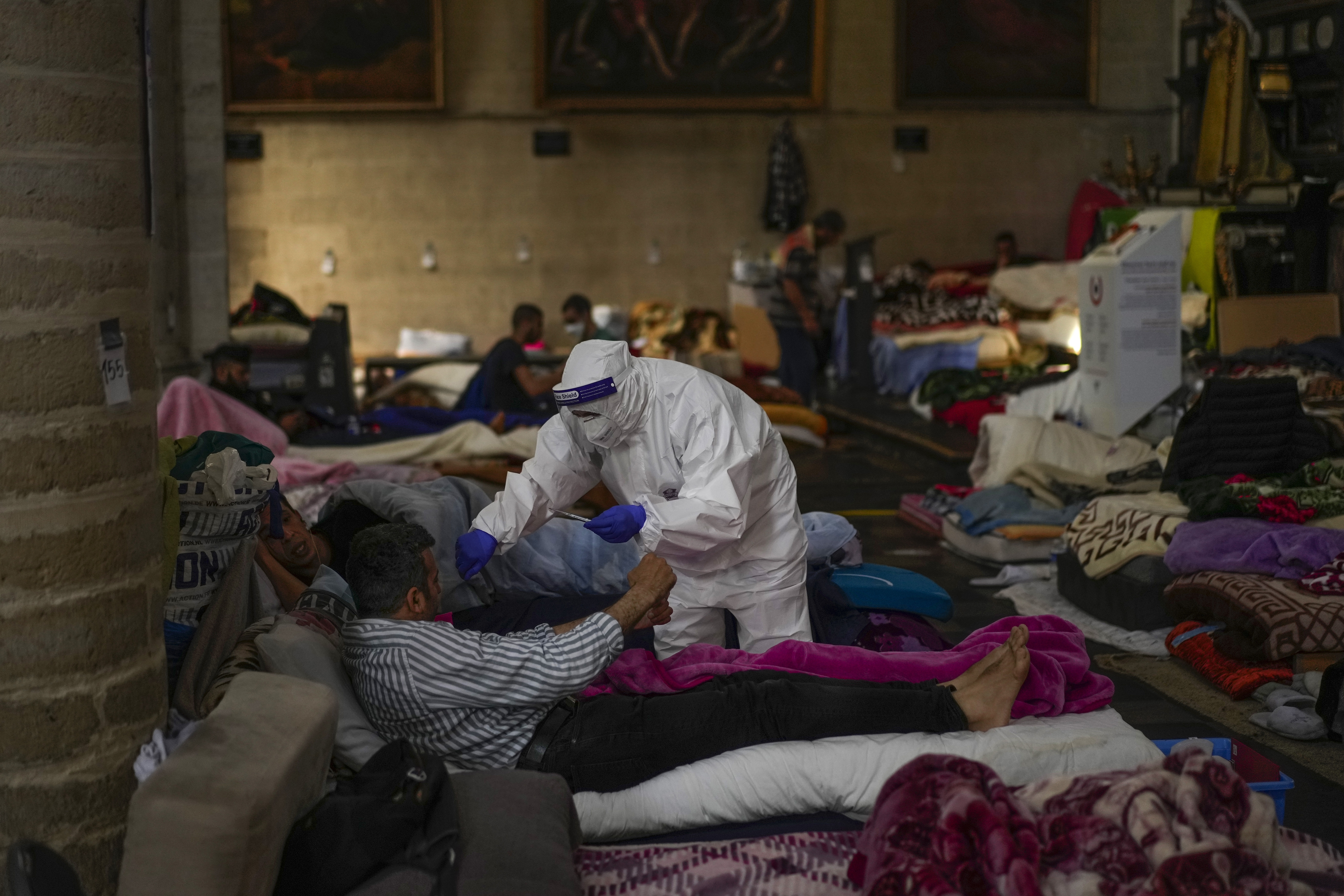 A Red Cross health worker attends a man on hunger strike at Saint-Jean-Baptiste-au-Beguinage church in Brussels in June.