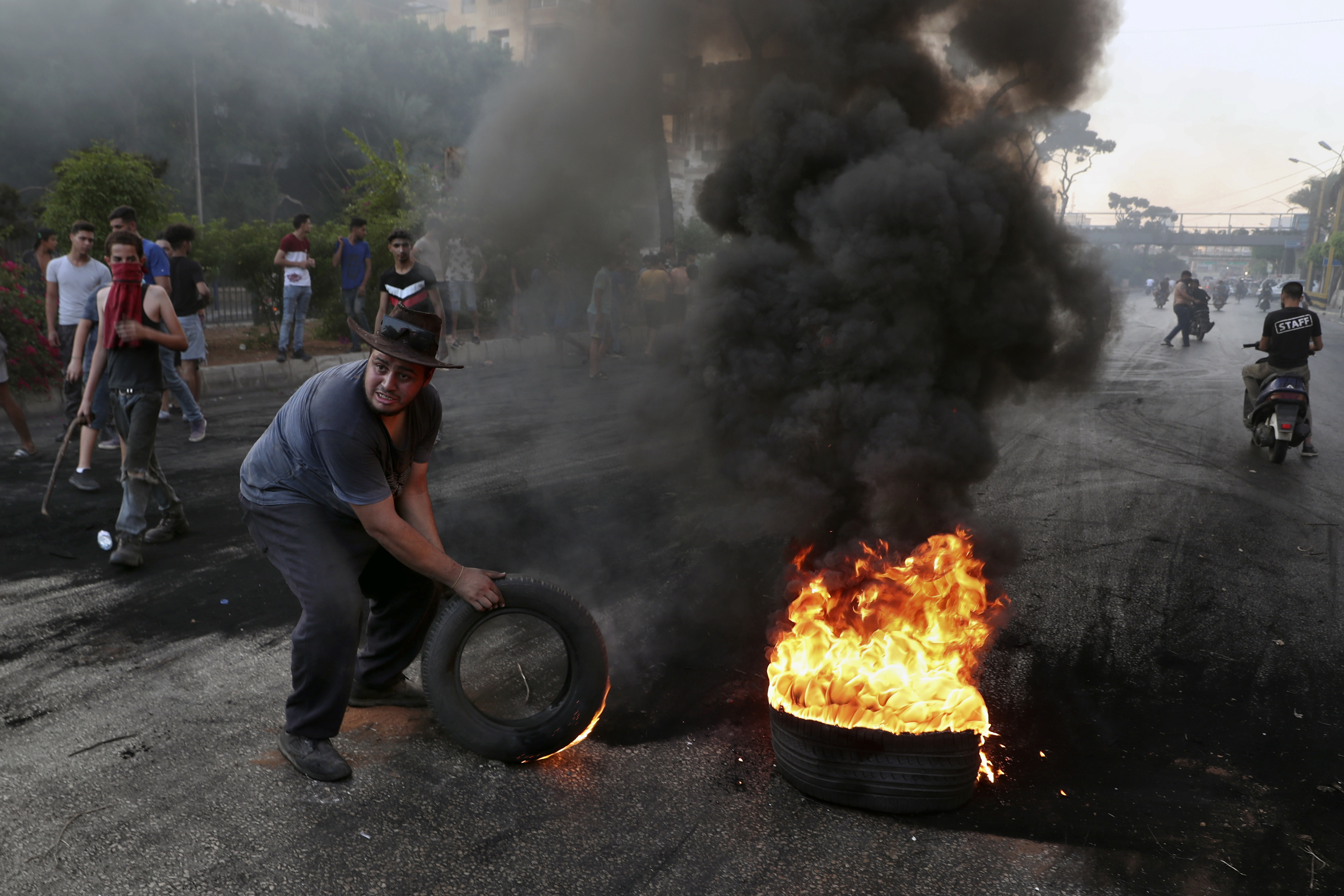 Protesters burn tires to block a road, in Beirut, Lebanon, last week.