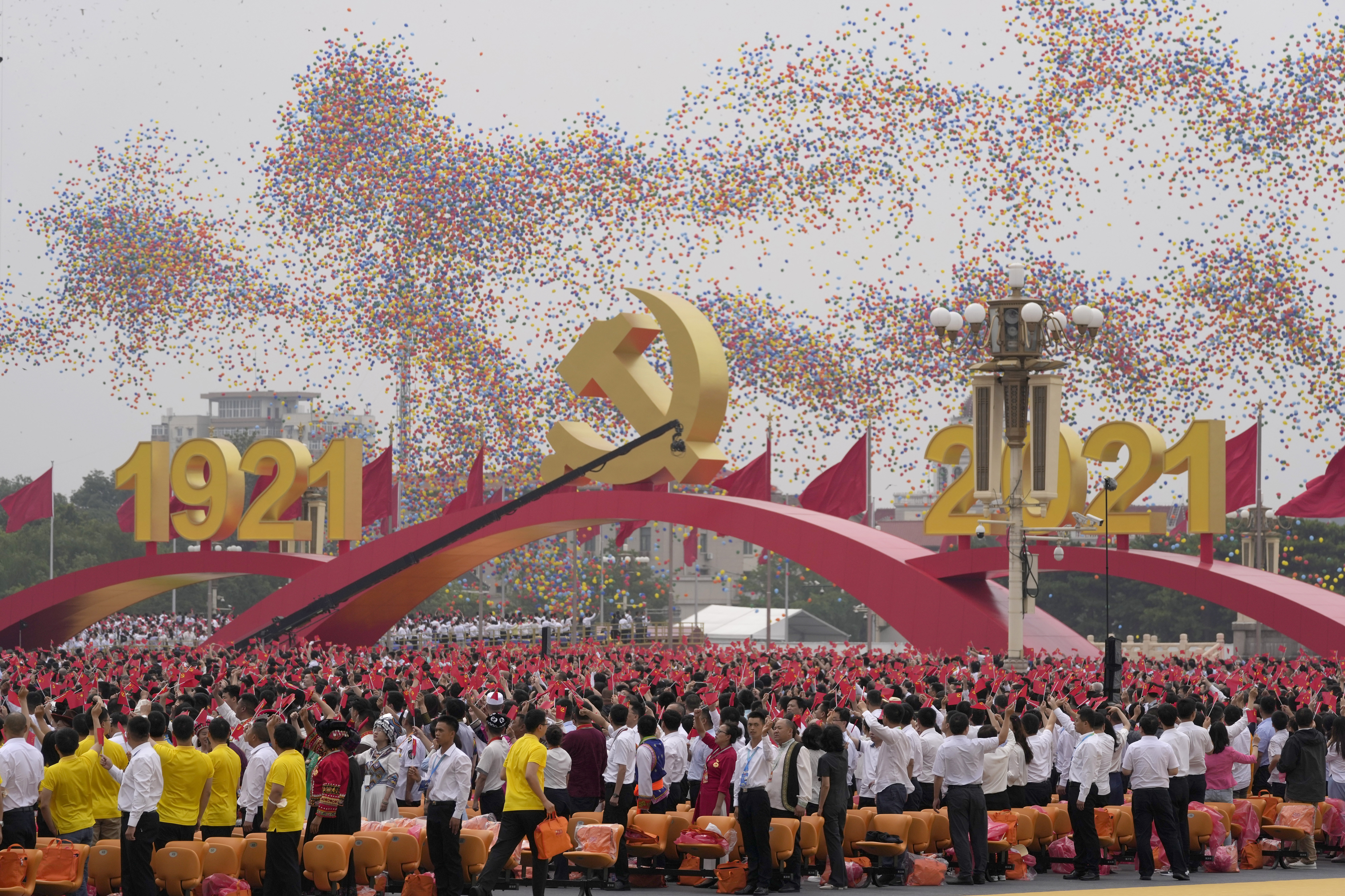 Balloons float over attendees waving Chinese flags during the anniversary celebration at Tiananmen Square on Thursday.