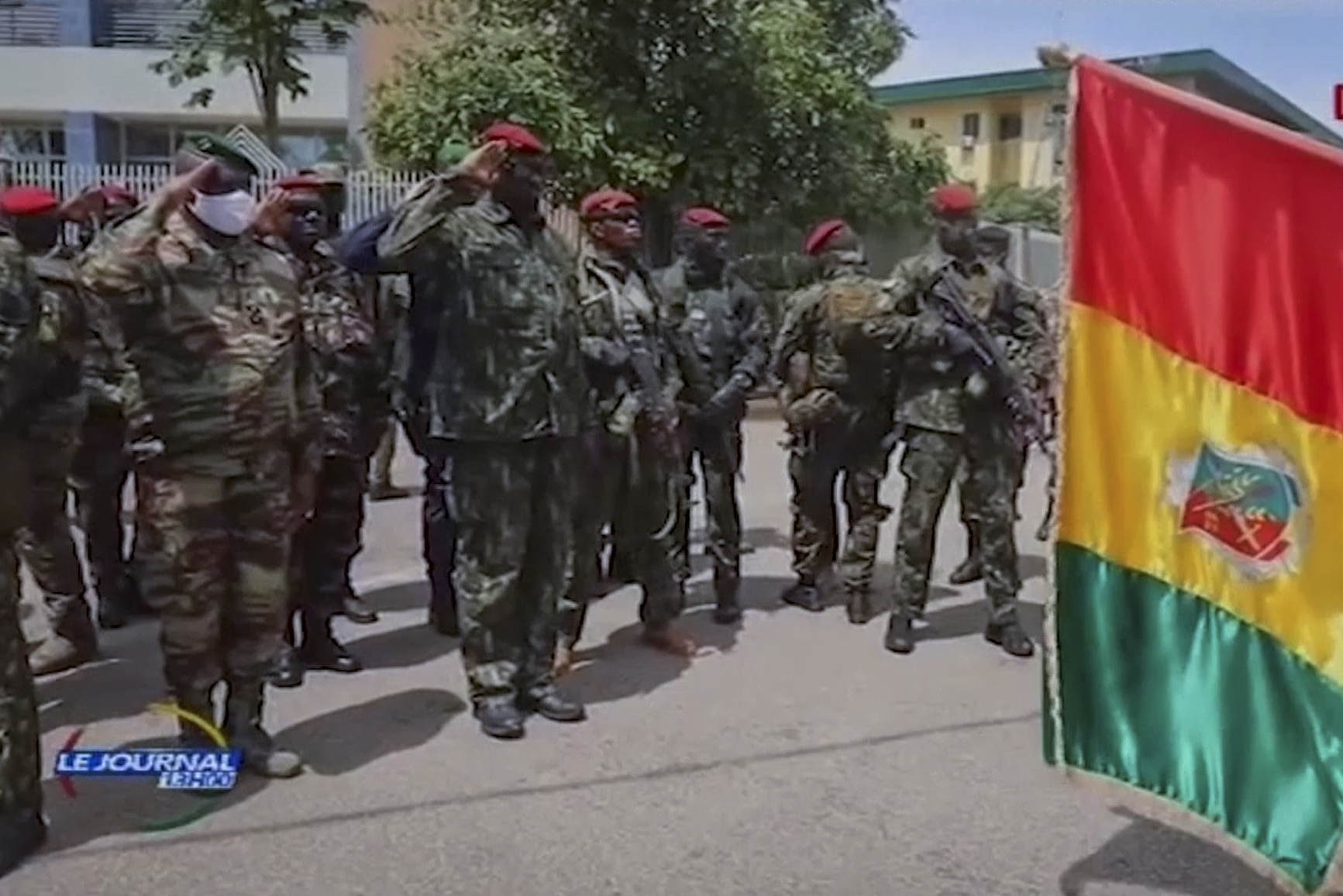 Col. Mamady Doumbouya (center left) salutes members of the armed forces in Conakry, Guinea, on Tuesday.