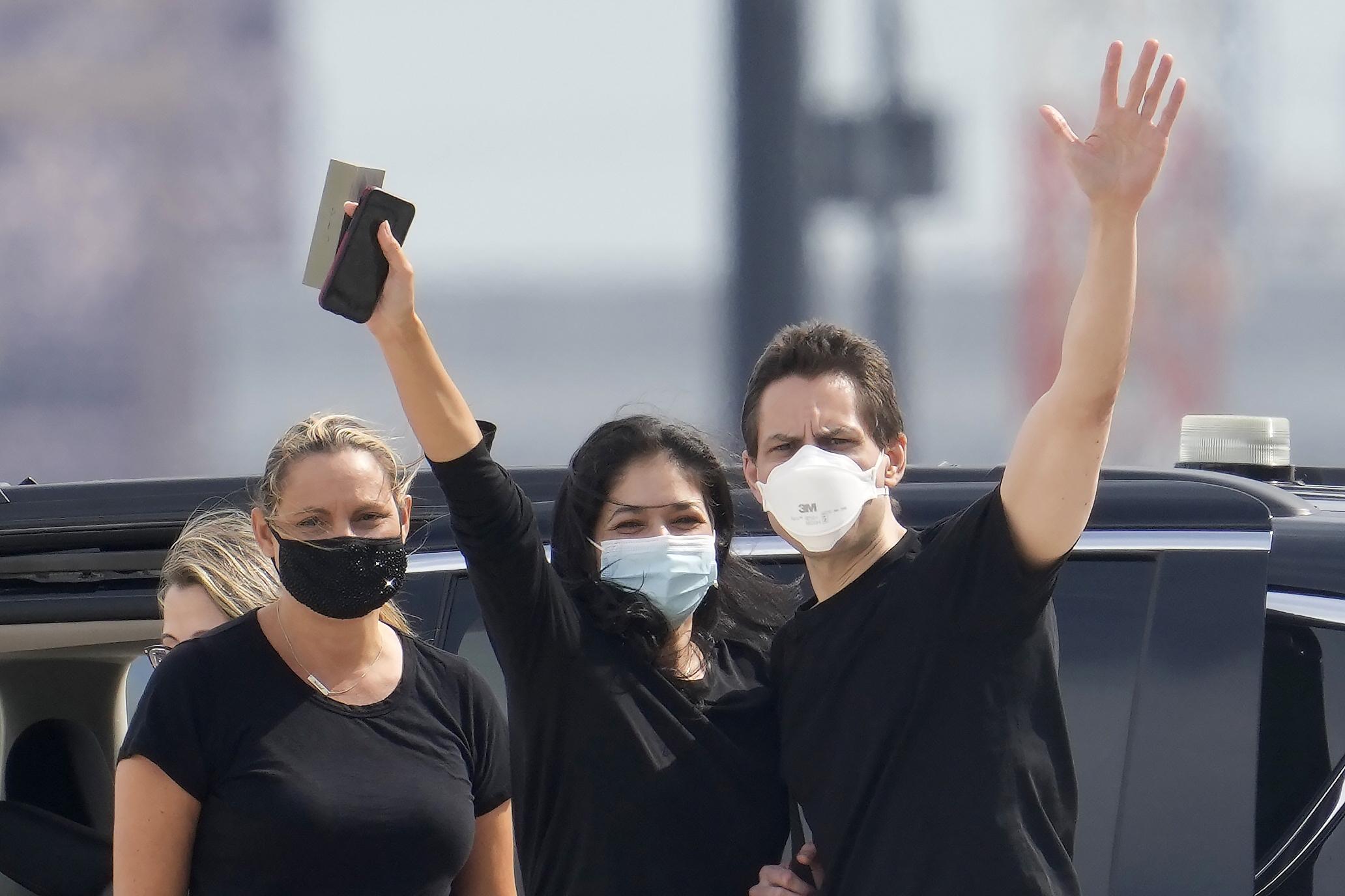 Michael Kovrig (right) with his wife Vina Nadjibulla (center) and sister Ariana Botha (left) at Pearson International Airport in Toronto on Saturday
