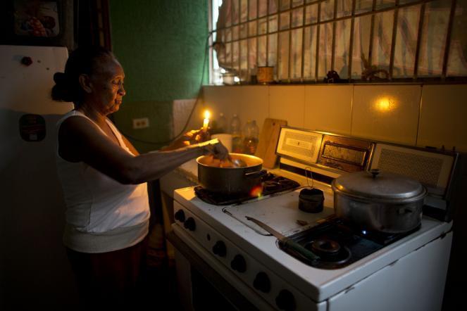 Ana Arroyo stirs a pot as she uses a candle to illuminate the area over the stove during a 2018 blackout in Maracaibo.