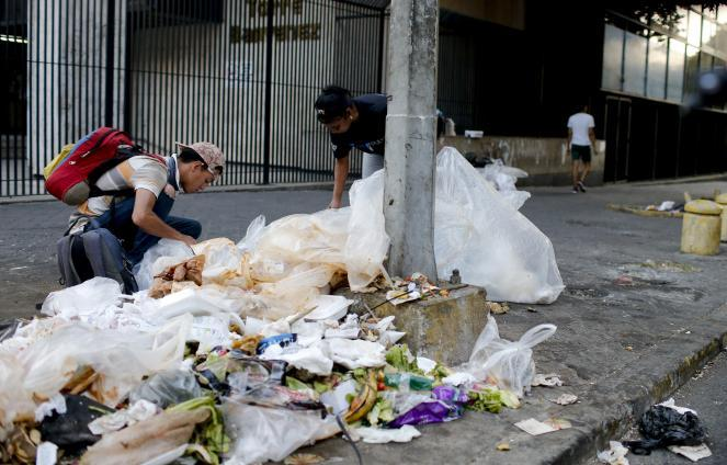 People search a garbage pile for food in Caracas.