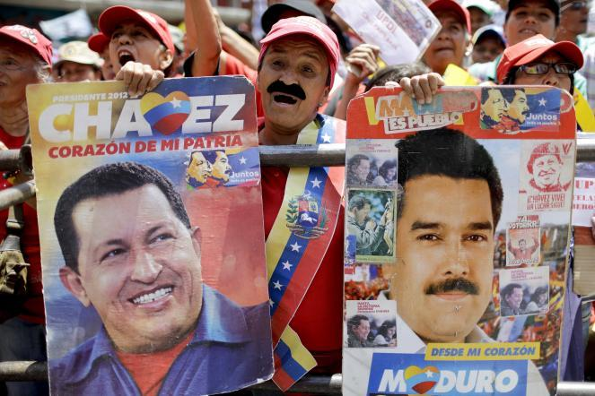 A government supporter holds posters depicting Chavez (left) and Maduro during a rally in Caracas.