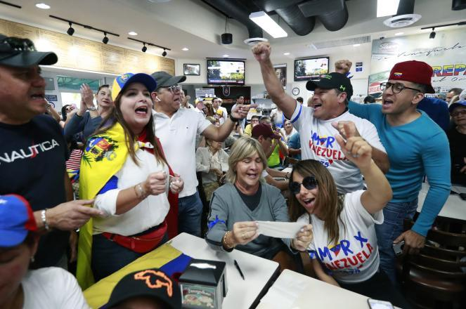 Venezuelans chant as they watch televised news from their country at the El Arepazo Doral Venezuelan restaurant in Doral, Fla.