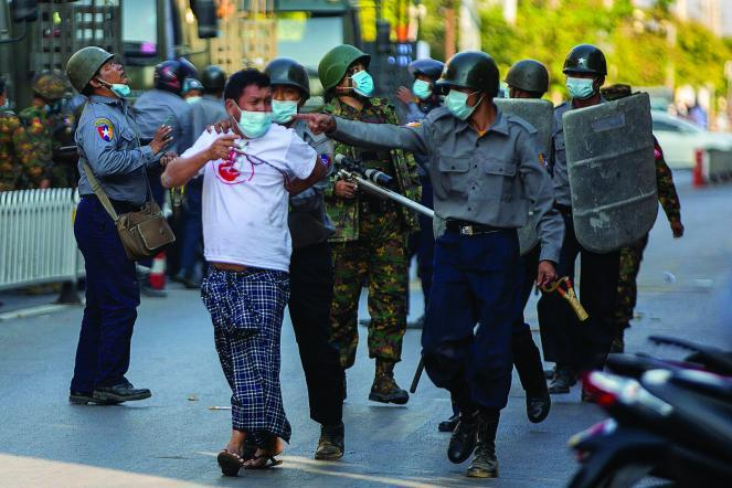 Police arrest a protester in Mandalay after the coup.