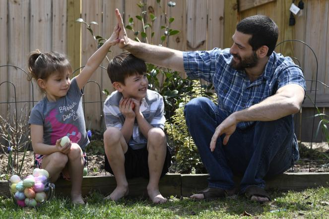 JP Rothenberg, right, gives daughter Evelynn, 5, a high five over the head of son Jack, 6, after completing an egg tapping battle in the backyard of their home in Glen Burnie, Md.