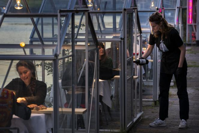 Staff at the Mediamatic restaurant serve food to volunteers seated in small glasshouses during a try-out of a setup for social distancing, abiding by government directives to combat the spread of the coronavirus in Amsterdam, Netherlands.