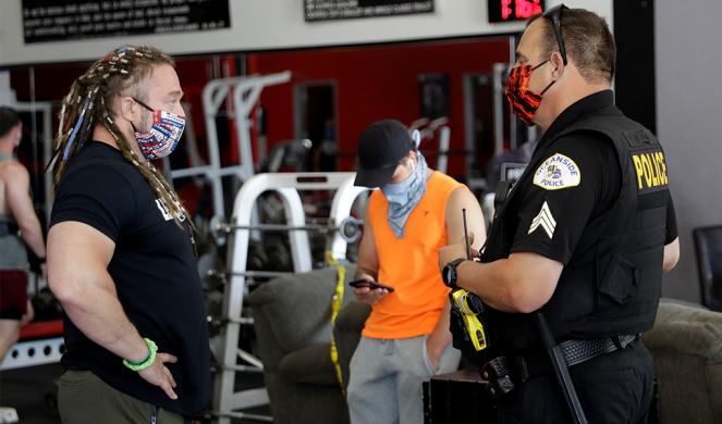 Lou Uridel, owner of Metroflex Gym, left, speaks with a police officer in Oceanside, Calif.