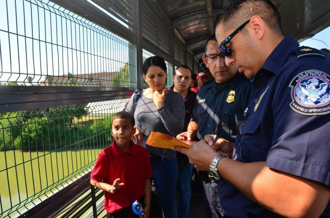 Customs and Border Protection agents process a Cuban family applying for U.S. asylum on an international bridge between Nuevo Laredo, Mexico, and Laredo, Texas.