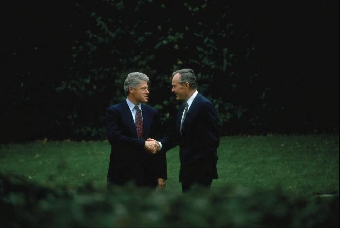 President George H.W. Bush and President-elect Bill Clinton shake hands during a stroll around White House grounds during a post-election visit by Clinton in 1992.