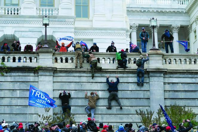 Rioters climb the west wall of the the U.S. Capitol on Jan. 6.