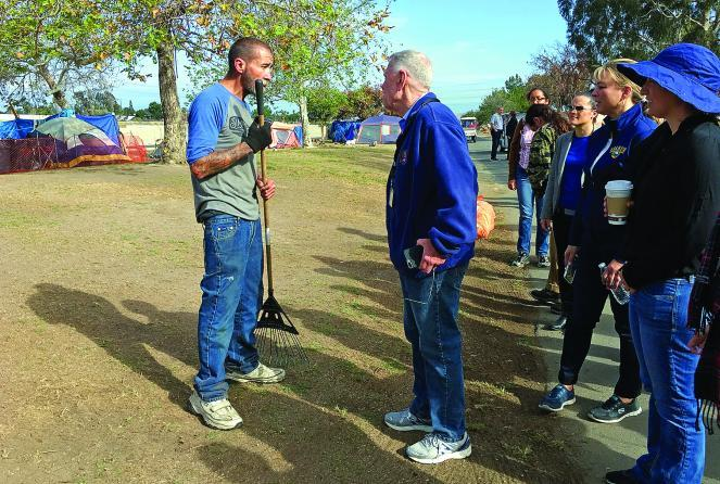 Judge Carter (in blue jacket) speaks with homeless resident Ronald Heatley during a tour of a homeless encampment along the Santa Ana River Trail in Anaheim.