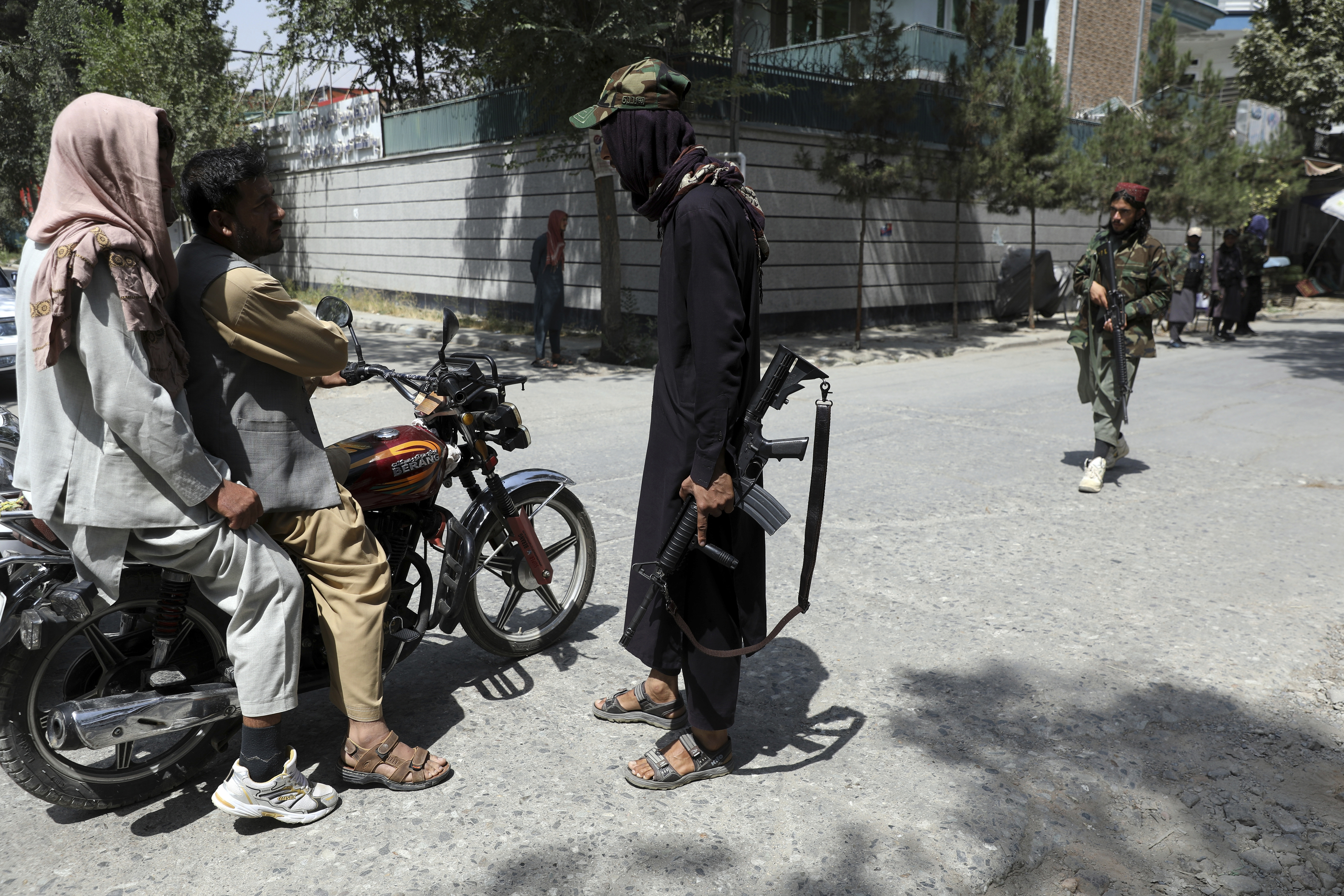 Taliban fighters stand guard at a checkpoint in the Wazir Akbar Khan neighborhood in Kabul.