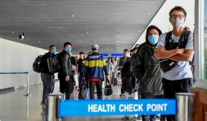 Passengers arriving from China wait in line to be checked by health officials at the Julius Nyerere International Airport in Dar Es Salaam.