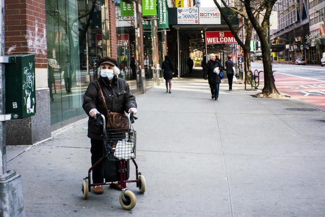 An elderly woman wears a face mask and plastic gloves as she waits to cross the street in New York City.