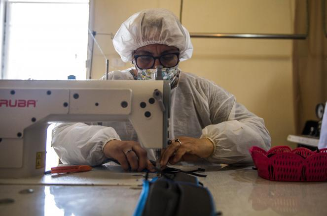A worker sews face masks in a factory in Le Bardo, outside Tunis, Tunisia, Monday, April 13.