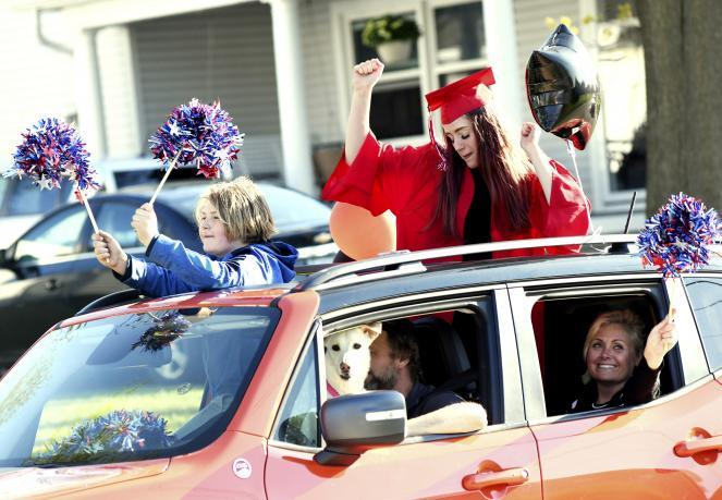 Jefferson High School senior Elle Vence, top right, dances through the sunroof with brother James, during a graduation parade in Jefferson, Ohio.