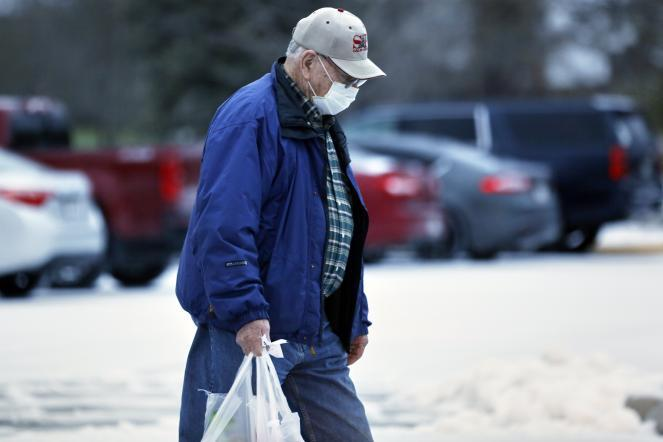 A shopper carries his groceries outside a supermarket in Omaha, Neb.