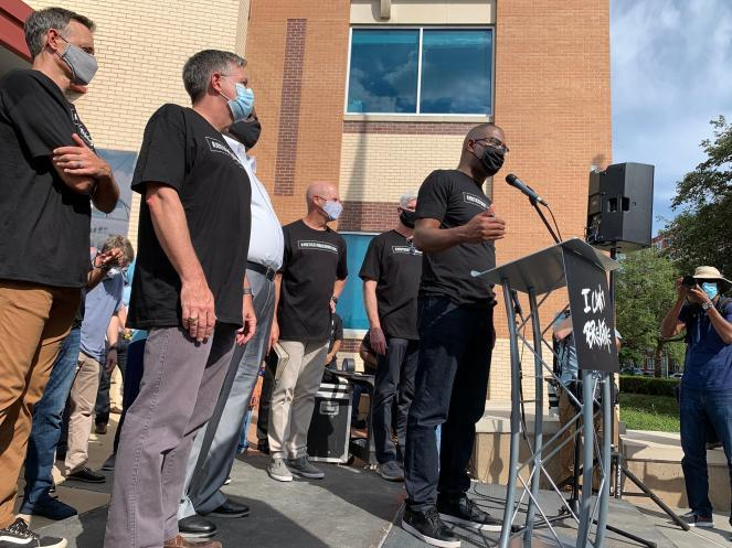 Pastor Bryan Carter stands among other Dallas clergy in front of police headquarters to speak to attendees of a prayer gathering.