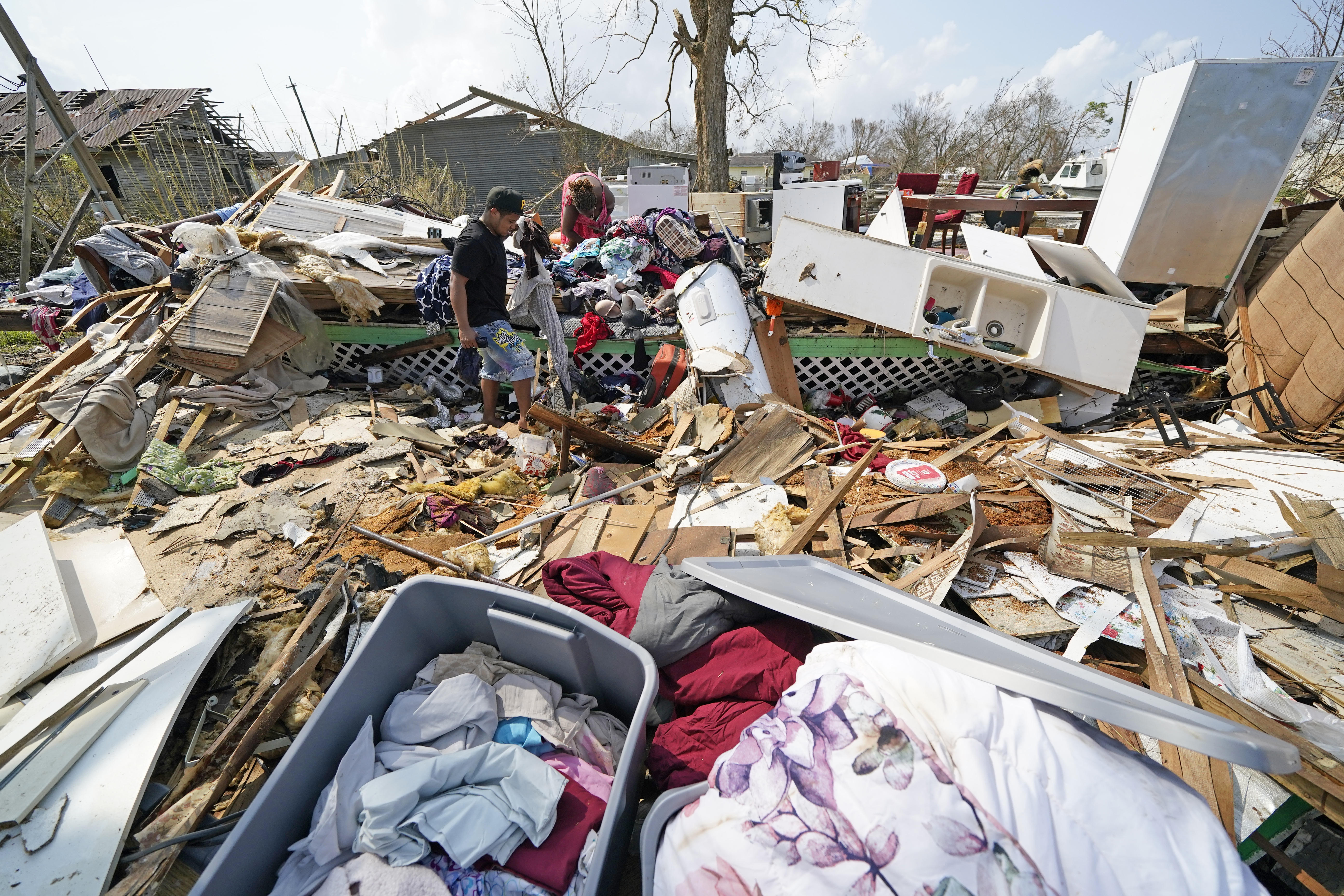 Jose Duran, left, helps his mother, Cruz Palma, sift through what remains of her home in Golden Meadow, La.