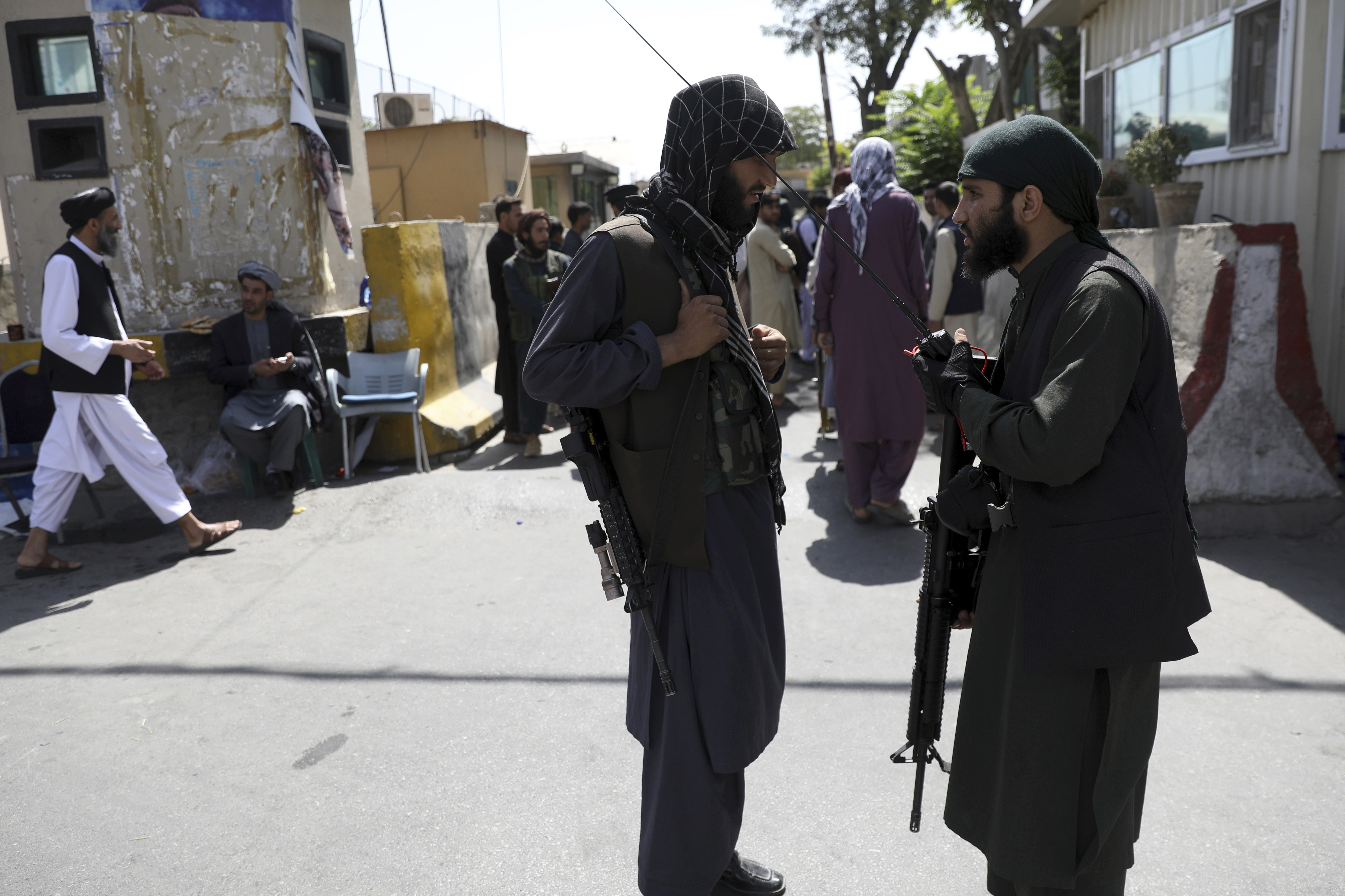 Taliban fighters stand guard in front of the main gate leading to Afghan presidential palace in Kabul.