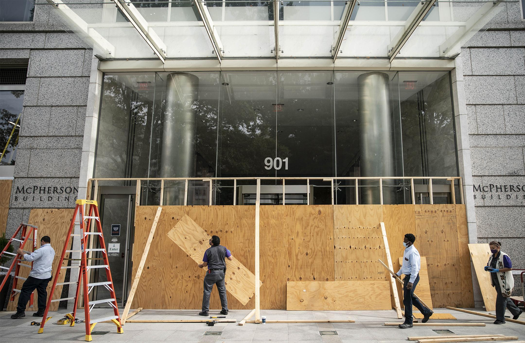 Workers place plywood on the front of the McPherson Building last week near the White House in Washington.