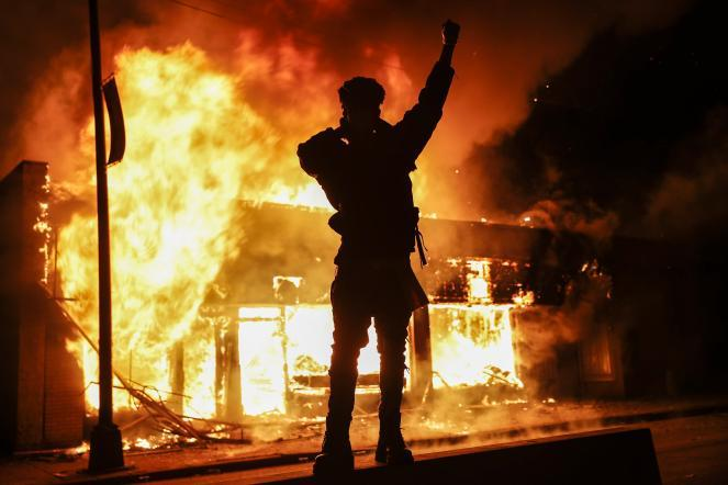A demonstrator stands beside a fire at a building that was once a check cashing business Saturday in St. Paul, Minn.