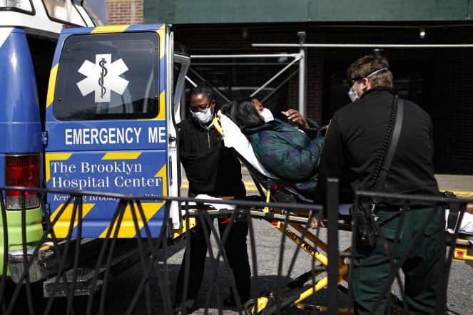 A patient wears a protective face mask as medical workers unload her from an ambulance at The Brooklyn Hospital Center emergency room in New York.