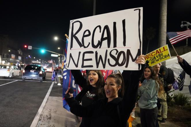 Demonstrators shout slogans while carrying a sign calling for a recall on Gov. Gavin Newsom during a protest against a stay-at-home order in Huntington Beach, Calif., on Nov. 21, 2020.