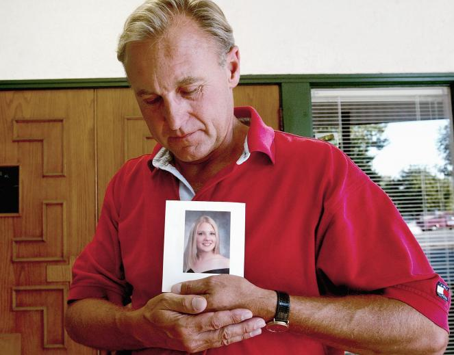 Monty Patterson holds a photograph of his daughter, Holly.