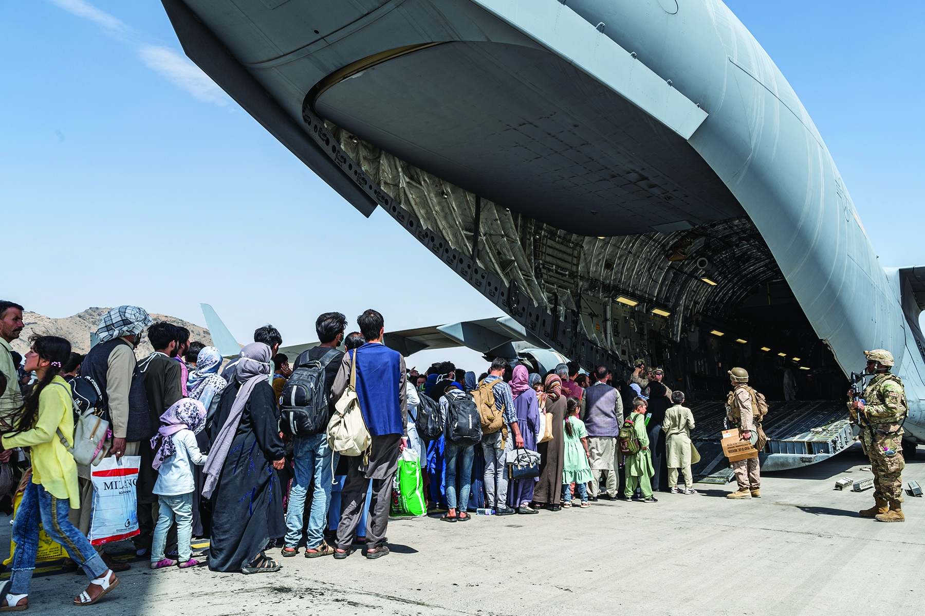 U.S. troops guide evacuees aboard a C-17 at Kabul's international airport.