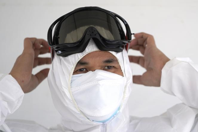 Registered nurse Louie Ambida puts on personal protective equipment before testing starts at a drive-thru testing site.