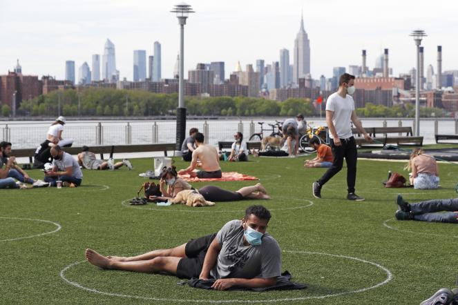 People relax in designated circles marked on the grass at Brooklyn's Domino Park.