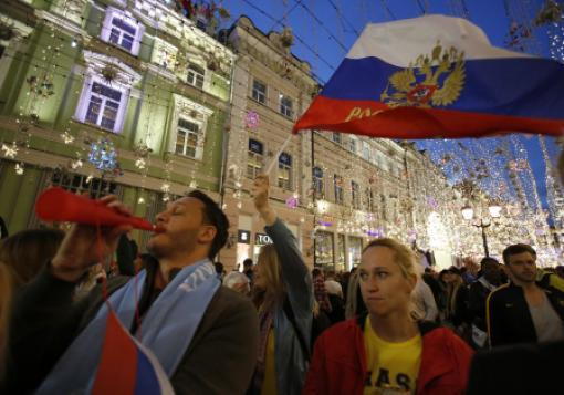 Russia fans celebrate their first World Cup soccer win Thursday in Moscow.