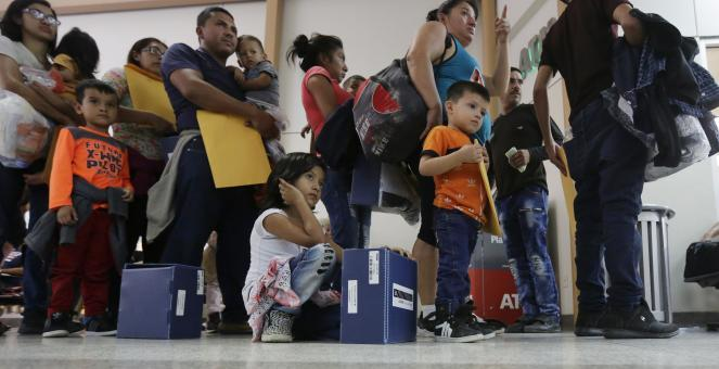 Asylum-seekers wait in line at a bus station after being processed and released by U.S. Customs and Border Protection in McAllen, Texas.