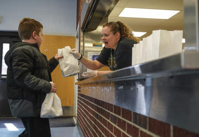 In Keego Harbor, Mich., Monday, Roosevelt Elementary School student Connor Hall picks up a lunch from West Bloomfield School District worker Melissa Gonzalez.