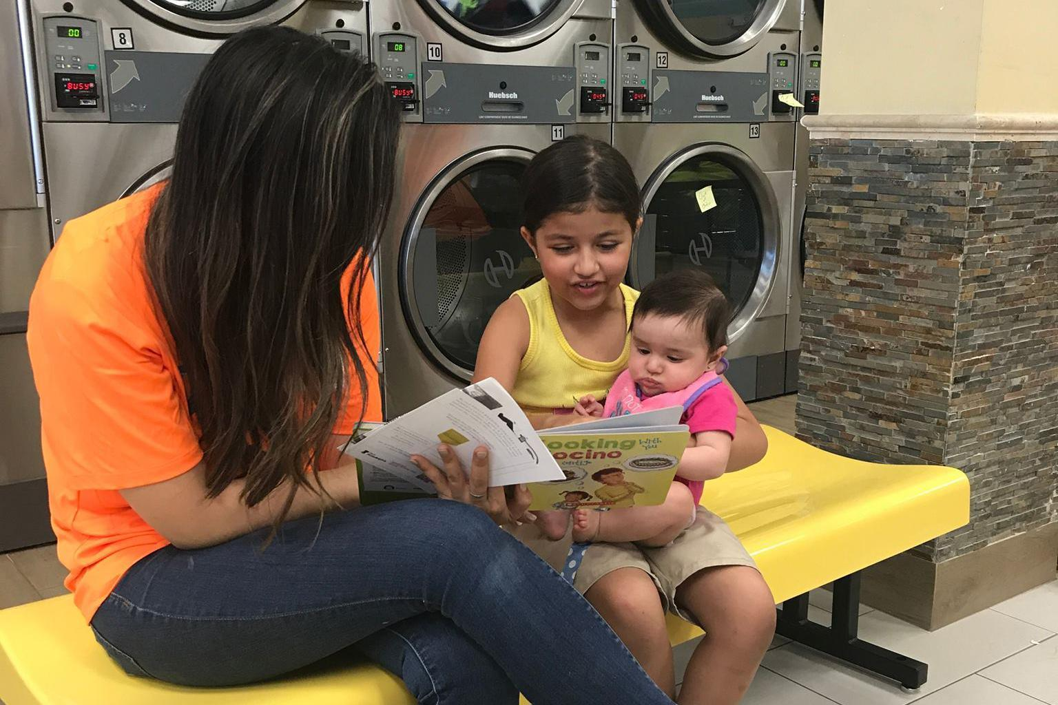 A family reads together at a laundromat