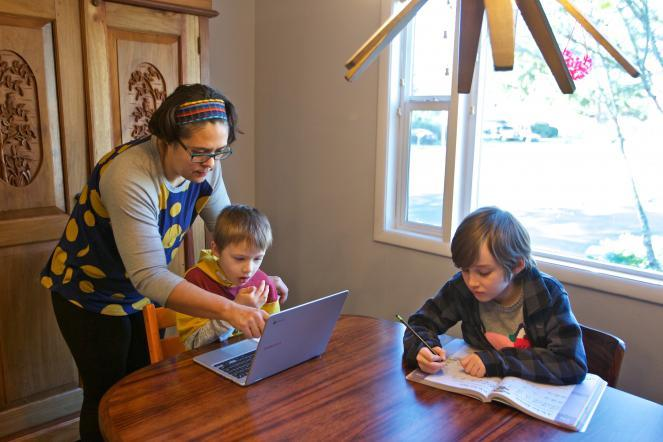 Olivia Bucks, left, helps her son Keith Bucks, center, with an online class assignment while Ashton Morris, right, works on a handwriting lesson from their first grade class at Arco Iris Spanish Immersion School in Beaverton, Ore.