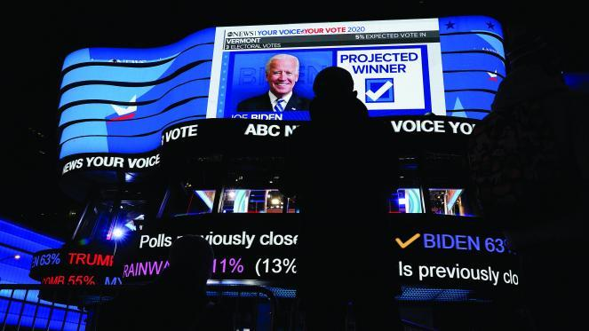 Pedestrians stop to watch early election results on the electronic billboards in Times Square in New York.