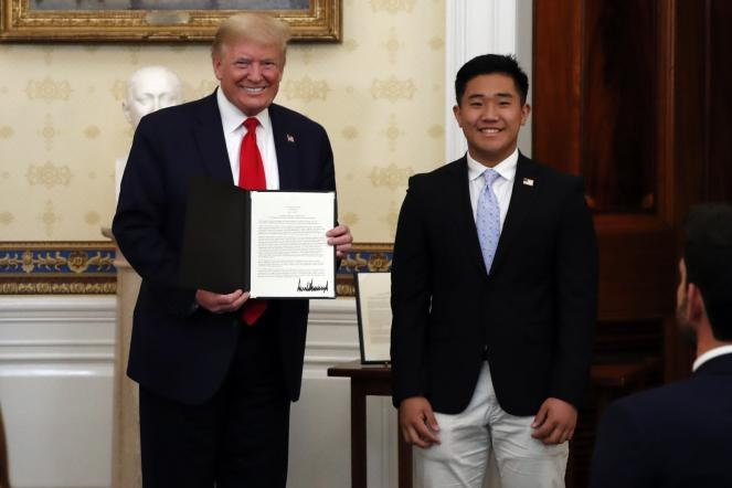 President Donald Trump poses for a photo with TJ Kim, a student pilot, during an event to honor volunteers helping to battle the coronavirus.