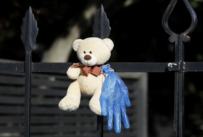 A teddy bear hangs on a fence outside a house in Christchurch, New Zealand. New Zealanders are embracing an international movement in which people are placing teddy bears in their windows during coronavirus lockdowns to brighten the mood and give children a game to play by spotting the bears in their neighborhoods.