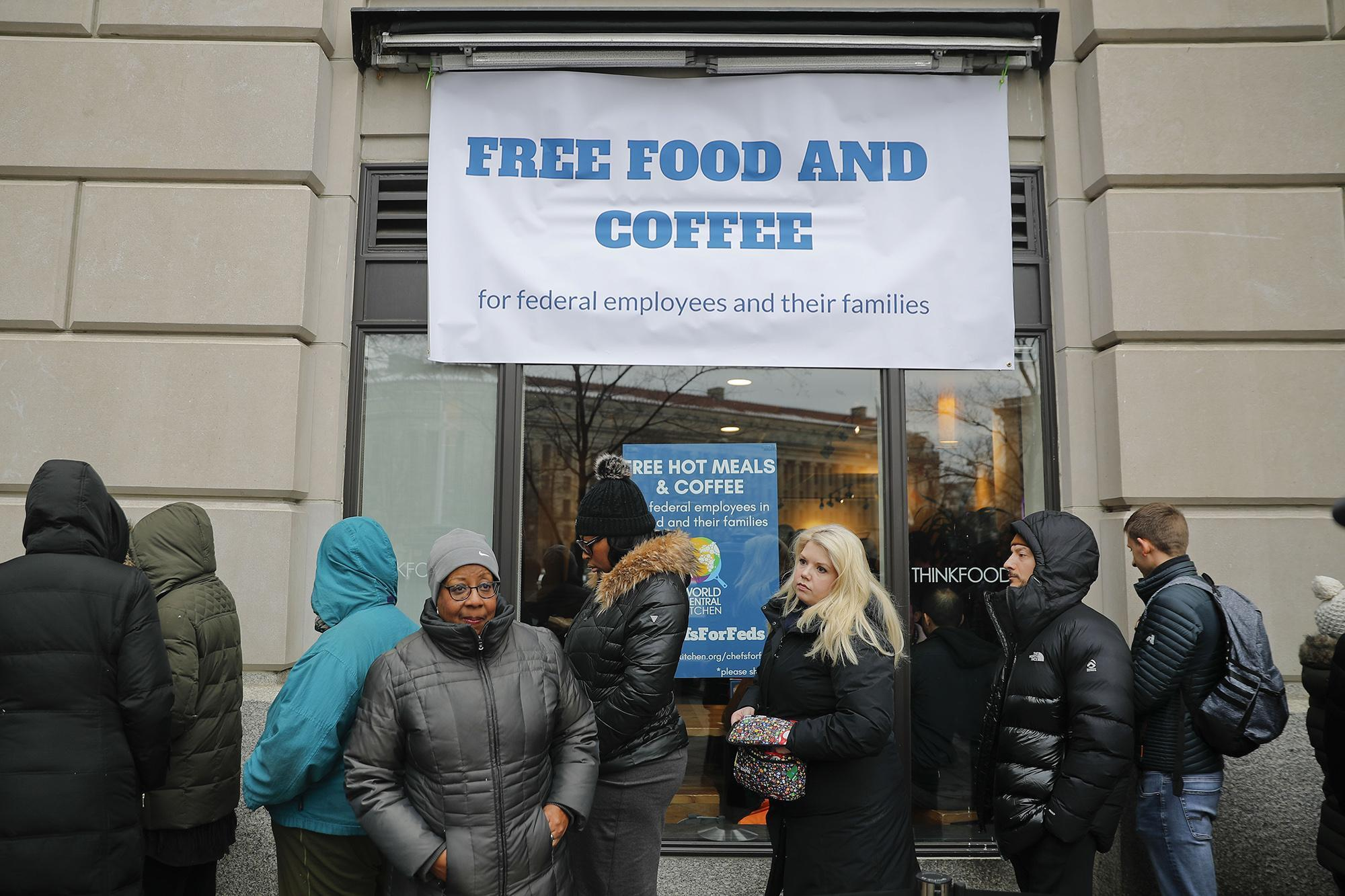 Federal workers wait in line at chef Jose Andres' World Central Kitchen for free meals Wednesday.