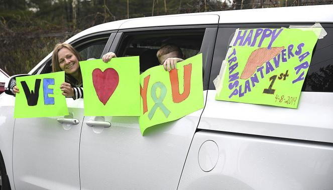 Courtney Ansley, of Stanaford, W.Va., left, and her son Mason, 10, display messages as they make a brief stop in a parade of cars past the home of Tammy Evans, who marked the one-year anniversary of her life-saving liver transplant.