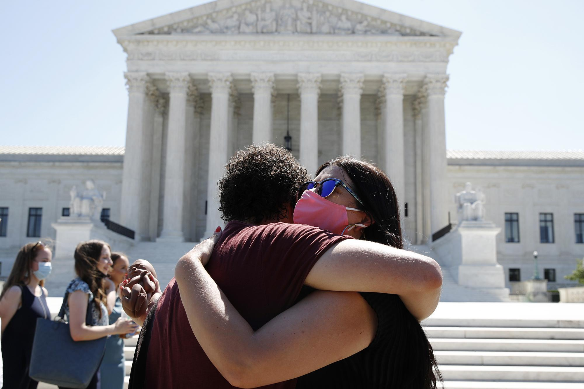 Pro-life demonstrators embrace outside of the Supreme Court on Monday.