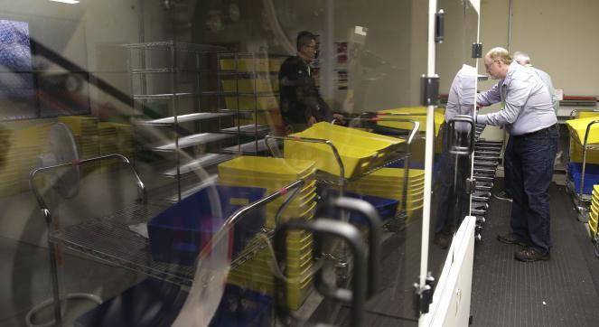 Temporary elections workers use a machine to scan signatures and sort mail-in ballots in Renton, Wash.