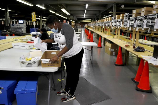 An elections assistant sorts mail-in ballots at a warehouse ahead of the 7th Congressional District special election in Baltimore.