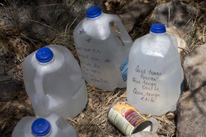 Water and empty cans of food sit along a trail near the border in Sasabe, Ariz.